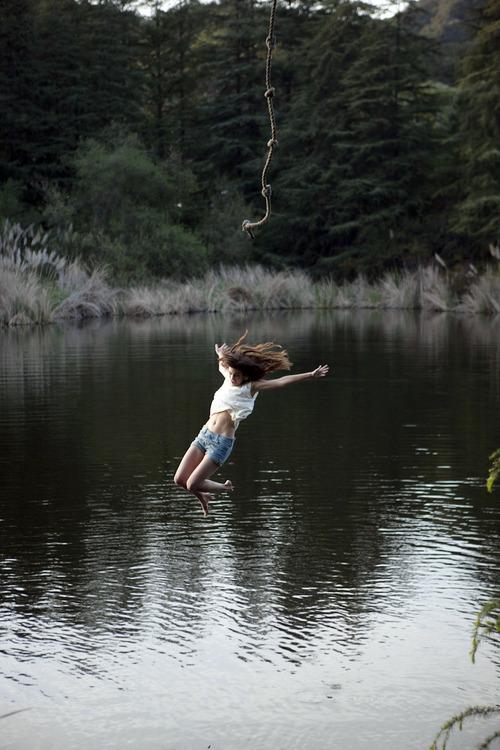 Woman jumping into lake